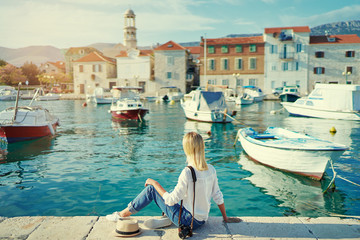 Tourism concept. Young traveling woman enjoying the view of Kastel Castle sitting near the sea on Croatian coast.