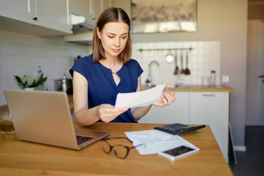 Thoughtful young woman using a laptop computer sitting at her kitchen holding utility bill and bank statements. Home interior.