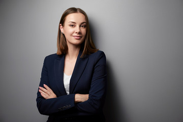 Fototapeta Confidence and charisma. Young business woman in suit looking at camera. Grey background. obraz