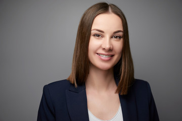 Confidence and charisma. Young businesswoman in suit looking at camera. Grey background.