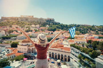Poster de jardin Athenes Enjoying vacation in Greece. Young traveling woman with national greek flag enjoying view of Athens city and Acropolis.