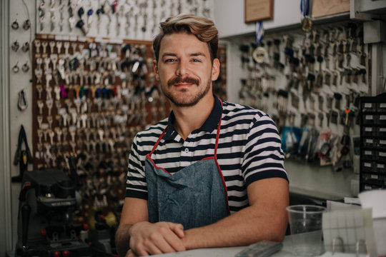 Handsome young locksmith is posing in his family shop