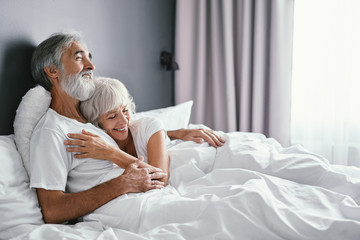 Obraz Happiness and tender. Senior family. Husbang hugging his wife in bed. - fototapety do salonu