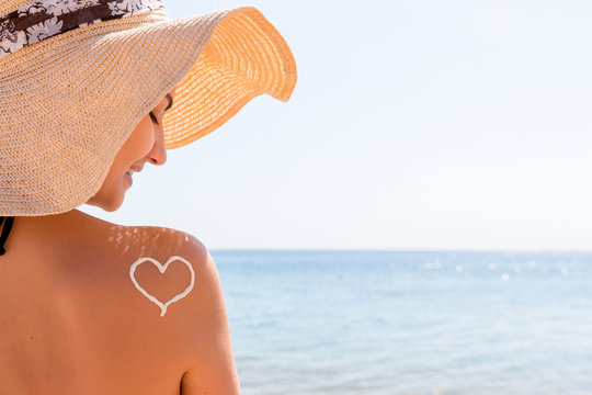 Heart made of sun cream is drawn on woman's shoulder at the beach