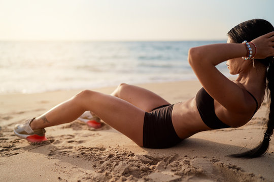 Abs workout - fitness woman working out on beach doing abs exercises for stomach weight loss toning.