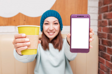 A young girl in a knitted hat drinks a hot drink and uses a mobile application on her smartphone