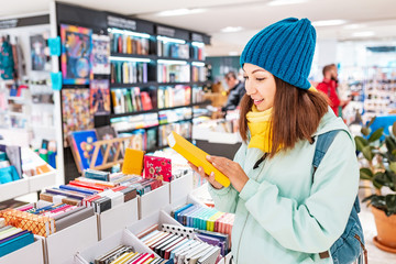 Young asian woman looking for a book in store