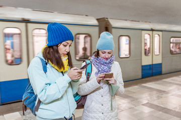Two girls friends using smart phone application at the metro station