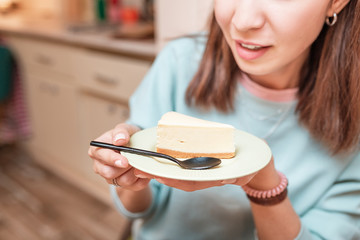woman tasting a piece of cheesecake