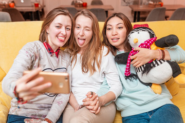 Female Friends relax on the couch and take a selfie