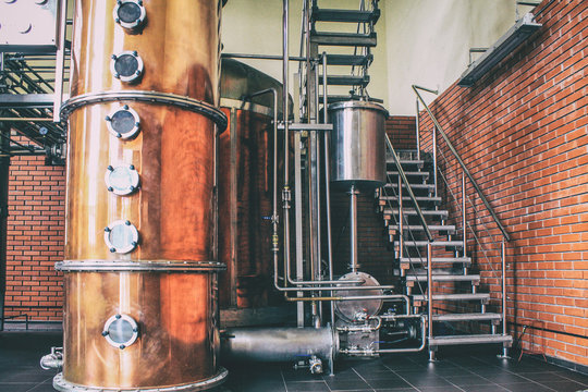 Industrial equipment for brandy production..Copper still alembic inside distiller to distill grapes and produce spirits.