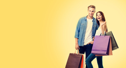 Photo of excited couple with shopping bags, over yellow color background