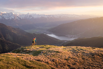 Male mountainbiker on a trail in the mountains at sunset