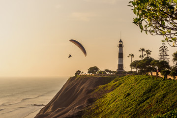 Paragliding on the cliffs of the city of Lima during sunset