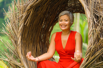 attractive and happy 40s or 50s middle aged Asian woman in classy and beautiful red dress practicing yoga relaxation and meditation in tropical jungle