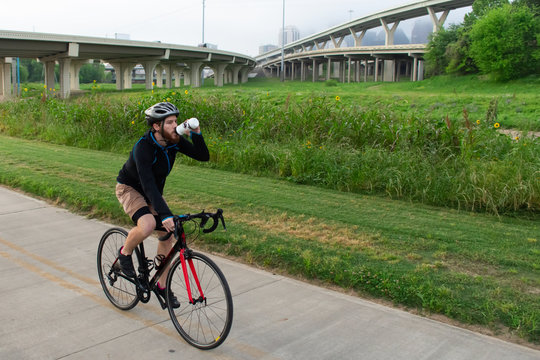 Man Biking and Drink Water on a Trail