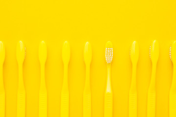 many new plastic yellow toothbrushes in a row on the yellow background. minimalist photo of toothbrushes turned down and one of them turned up. flat lay image of toothbrushes with copy space