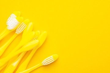many new plastic yellow toothbrushes on the yellow background with copy space