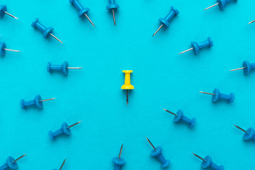 yellow push pin in the center of blue push pins with their spike turned to the yellow one as a concept of bullying or discrimination. conceptual photo of attack on person for opinion or views
