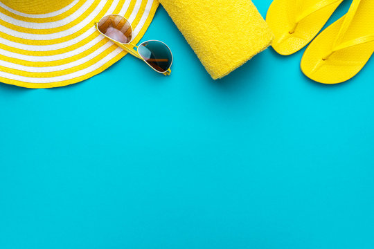 yellow beach accessories on turquoise blue background - sunglasses, towel. flip-flops and striped hat. summer is coming concept with copy space. holiday by the sea concept.