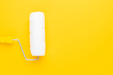 clean paint roller with yellow handle on the yellow background. minimalist photo of paint roller with copy space