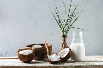 Variety of coconut products milk in glass bottle, oil and flakes in shell, fresh broken coconut on old wooden table with grey wall at background. Healthy eating, copy space