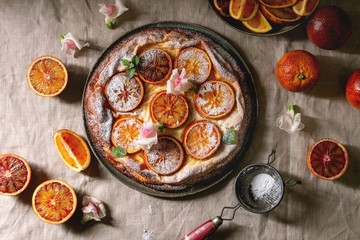 Homemade Cheesecake with sicilian blood oranges, decorated by edible flowers, mint leaves and sugar powder served in plate with cutted oranges above over grey linen table cloth. Flat lay, space