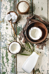Variety of coconut products milk in glass bottle, oil and flakes in shell, fresh broken coconut on old wooden plank background. Healthy eating. Flat lay, space