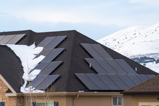 Solar panels installed on the dark roof of a home with snow in winter