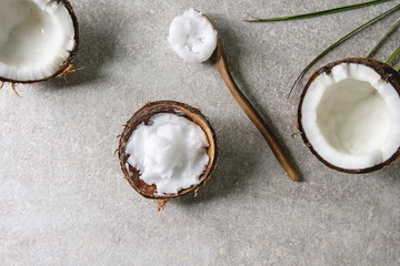 Organic vegan cold pressed coconut oil in coconut shell and wooden spoon over grey texture background. Healthy eating. Flat lay, copy space
