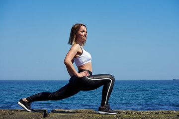 Horizontal photo of a beautiful woman who does sports exercises on the beach of the ocean or sea. The woman doing squats exercises.