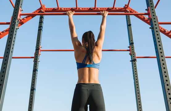Rear view of fit young female doing pull ups exercises on crossbar outdoors. Athlete woman training hard on the bar at sportground. People, sport anh healthy lifestyle concept