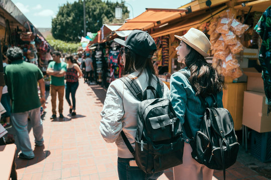 back view of two asian girls best friends travel in los angeles together on summer break. young women tourist backpacker shopping in mexico outdoor market. ladies walking in olvera street having fun.