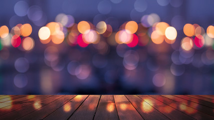 Empty wooden table with blurred cityscape, blurred city lights reflected on wooden background. Empty background template with bokeh Fotomurales