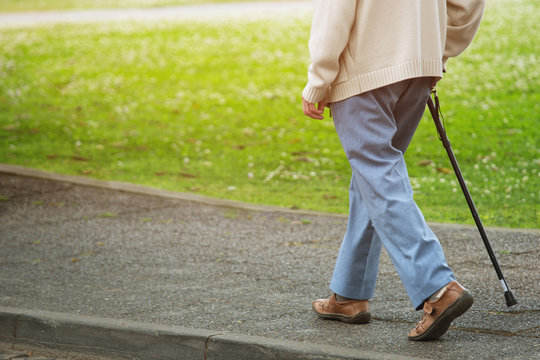 elderly old man with walking stick stand on footpath sidewalk crossing the street alone roadside in public park. concept senior across the street. soft focus