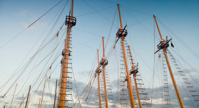 Image of high wooden masts of old ships in port against blue sky at evening