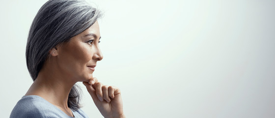 Pensive woman is touching chin and slightly smiles Fototapete