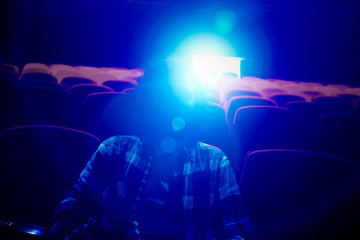 A spectator in an empty movie theater with projection light falling into the lens