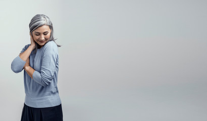 Happy woman is hugging herself on white background