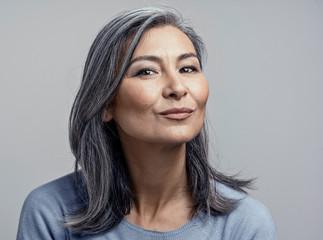 Charming Asian mature woman smiles at camera