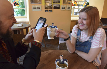 Customers take pictures of a tag of a green tea bag with Ukrainian President-elect Zelenskiy's image at a cafe in Lviv