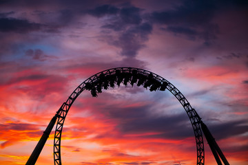 Tuinposter Amusementspark Silhouette of people having fun on a roller-coaster in an amusement park at sunset. Adrenalin concept.