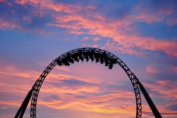 Foto auf AluDibond Vergnugungspark Silhouette of people having fun on a roller-coaster in an amusement park at sunset. Adrenalin concept.