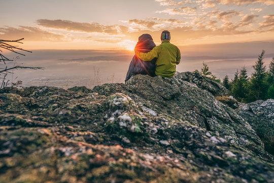 Two people in sleeping bag sitting on the rock watching sunset or sunrise. Romantic view from sleeping bag in the mountain landscape. Sun rising, dramatic sky. Camping in the outdoors.