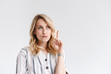 Portrait of young blond woman wearing casual clothes looking at copyspace and pointing finger upward