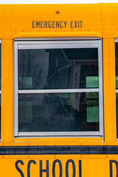 Exterior of a yellow school bus with a close up view of its glass window