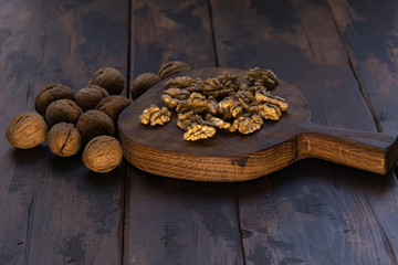 Cracked and whole walnuts lying on cutting board and wooden table, side view. Healthy nuts and seeds composition.