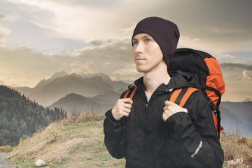 Active young man hiking in the mountain, side view on cloudy landscape background. Active lifestyle and tourism concept.