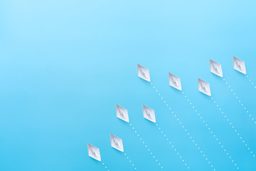 White paper ships on blue background. Business competition concept.