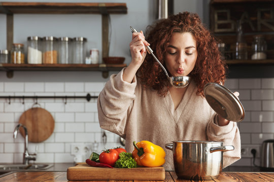 Photo of pretty caucasian woman holding cooking ladle spoon while eating soup at home